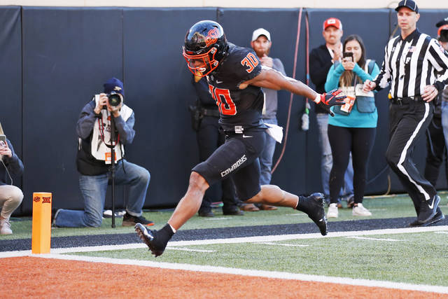 Oklahoma State running back Chuba Hubbard (30) leaps into the end zone with a touchdown in the second half of an NCAA college football game against TCU in Stillwater, Okla., Saturday, Nov. 2, 2019. (AP Photo/Sue Ogrocki)