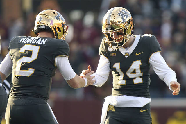 Minnesota quarterback Tanner Morgan (2) celebrates with teammate Casey O'Brien (14) after their team scored a touchdown against Maryland during an NCAA college football game Saturday, Oct. 26, 2019, in Minneapolis. (AP Photo/Stacy Bengs)
