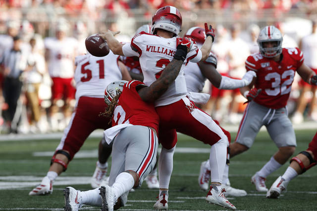 "FILE - In this Sept. 21, 2019, file photo, Ohio State defensive end Chase Young, left, sacks Miami (Ohio) quarterback Jackson Williamson causing a fumble during the first half of an NCAA college football game, in Columbus, Ohio. Ohio State says defensive end Chase Young won't play Saturday against Maryland because of a possible NCAA ""issue"" in 2018. The surprising news was announced by the school with team's status report and depth chart for the coming game. The statement says Young is being held out because of a ""possible NCAA issue from last year"" the athletic department is ""looking into."" (AP Photo/Jay LaPrete, File)"
