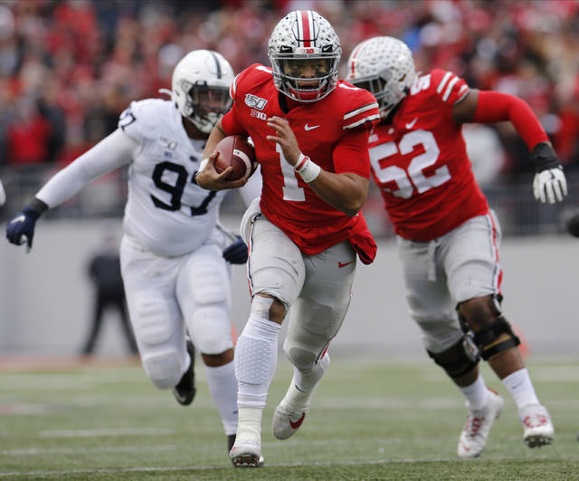 Ohio State quarterback Justin Fields, center, runs for a first down against Penn State during the first half of an NCAA college football game Saturday, Nov. 23, 2019, in Columbus, Ohio. (AP Photo/Jay LaPrete)