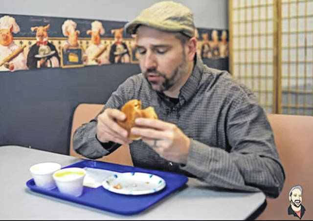 "Matt Beireis admires a Beaugard's sandwich for a ""Clinton County Best Restaurants"" video produced by him and by David Fall."