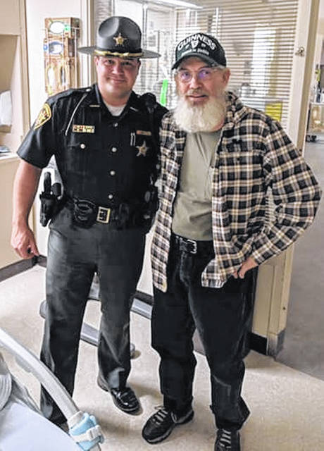 James Harris, right, stands next to Clinton County Sheriff's Deputy Thomas Couch, who aided James' wife, Sheila, when she suffered a cardiac arrest.