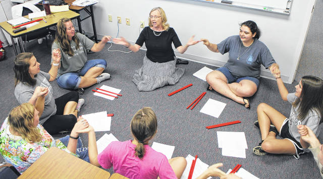 Becky Storer, seated at left beneath whiteboard, sings with students at Southern State Community College in Hillsboro.
