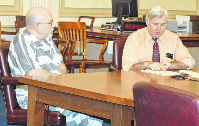 Prior to his Thursday court hearing, Terrin R. Long, left, listens to his attorney Clinton County Public Defender Rob Baker.