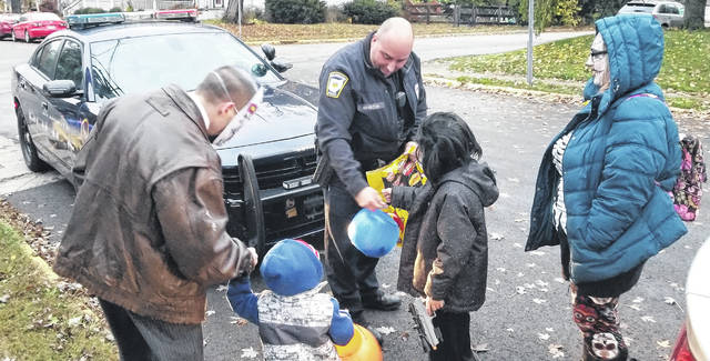 Officer Hamilton of the Wilmington Police Department passes out Halloween candy to neighborhood children on North Walnut Street in the city.