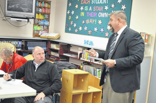 East Clinton High School Principal Michael Adams, right, reports to the school board. At left are board members Greg Bronner, foreground, and Tim Starkey, reading behind him.