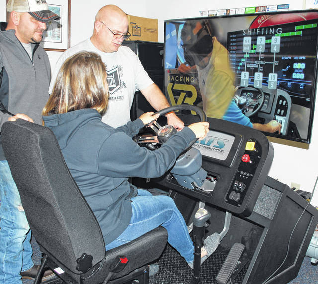 JT Smith, Southern State Truck Driving Academy Director/Training Manager, works with a student on a virtual-reality simulator that allows for shifting and driving training without getting behind the wheel.