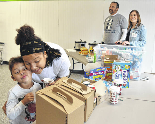 At the Wilmington Church of God's free food and drinks tables Saturday inside Anytime Laundry, Zyde Kemp and Kyara Turner snuggle in the foreground while church volunteers Bill Davis and Autumn Allen stand ready to provide hot dogs.