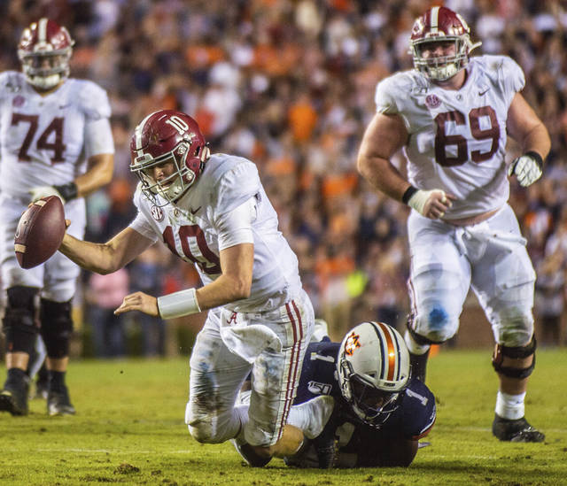 Alabama quarterback Mac Jones (10) is sacked by Auburn defensive end Big Kat Bryant (1) during the second half of an NCAA college football game Saturday, Nov. 30, 2019, in Auburn, Ala. (Dan Busey/The Decatur Daily via AP)