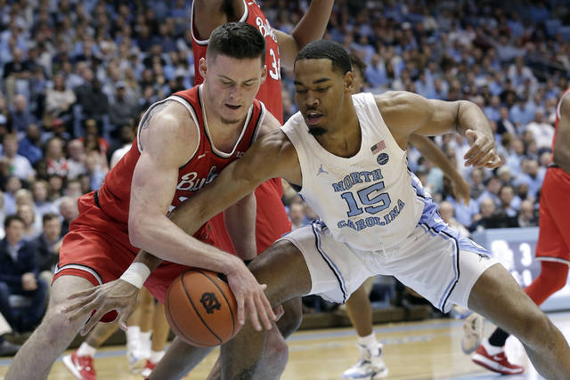 Ohio State forward Kyle Young, left, and North Carolina forward Garrison Brooks (15) reach for the ball during the first half of an NCAA college basketball game in Chapel Hill, N.C., Wednesday, Dec. 4, 2019. (AP Photo/Gerry Broome)