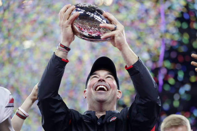 Ohio State coach Ryan Day holds the trophy following the team's 34-21 win over Wisconsin in the Big Ten championship NCAA college football game, early Sunday, Dec. 8, 2019, in Indianapolis. (AP Photo/Michael Conroy)