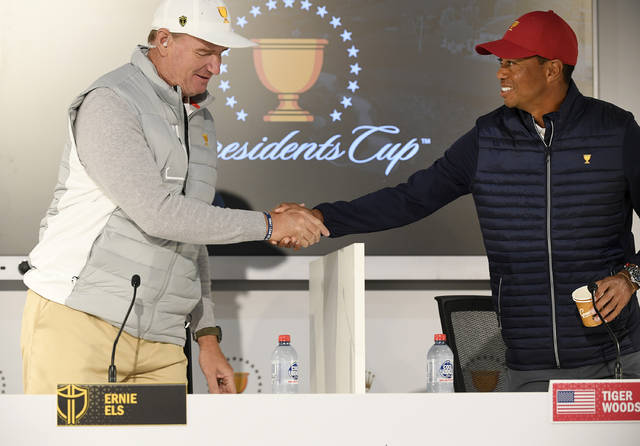 International captain Ernie Els, left, and USA captain Tiger Woods shake hands during a press conference ahead of the President's Cup Golf tournament in Melbourne, Australia, Tuesday, Dec. 10, 2019. (AP Photo/Andy Brownbill)
