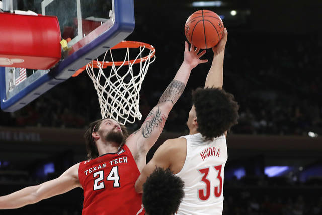 Texas Tech guard Avery Benson (24) defends against a shot by Louisville forward Jordan Nwora (33) during the first half of an NCAA college basketball game in the Jimmy V Classic, Tuesday, Dec. 10, 2019, in New York. (AP Photo/Kathy Willens)