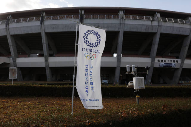A Tokyo 2020 banner stands in front of the Azumi Baseball Stadium, a venue for baseball and softball at the Tokyo 2020 Olympics, Saturday, Nov. 30, 2019, in Fukushima, Fukushima prefecture, Japan. The torch relay for the Tokyo Olympics will kick off in Fukushima, the northern prefecture devastated almost nine years ago by an earthquake, tsunami and the subsequent meltdown of three nuclear reactors. (AP Photo/Jae C. Hong)