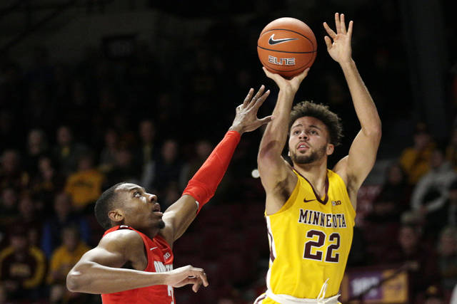Minnesota guard Gabe Kalscheur (22) shoots over Ohio State guard D.J. Carton in the first half of an NCAA college basketball game Sunday, Dec. 15, 2019, in Minneapolis. (AP Photo/Andy Clayton-King)