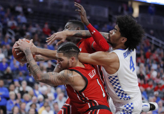 Kentucky's Nick Richards (4) fouls Utah's Timmy Allen (1) during the second half of an NCAA college basketball game Wednesday, Dec. 18, 2019, in Las Vegas. (AP Photo/John Locher)