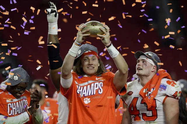 Clemson quarterback Trevor Lawrence holds up the trophy after Clemson's 29-23 win over Ohio State in the Fiesta Bowl NCAA college football playoff semifinal Saturday, Dec. 28, 2019, in Glendale, Ariz. (AP Photo/Rick Scuteri)