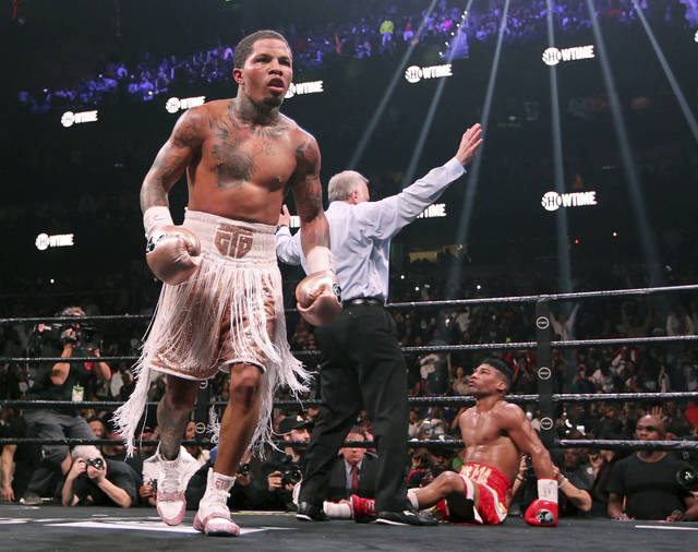 CORRECTS SURNAME OF REFEREE TO REISS, INSTEAD OF WEISS - Gervonta Davis, left, heads to the corner as Yuriorkis Gamboa, right, looks up at referee Jack Reiss during the WBA secondary lightweight title boxing bout early Sunday, Dec. 29, 2019, in Atlanta. Davis won when the fight was stopped in the 12th round. (AP Photo/Tami Chappell)