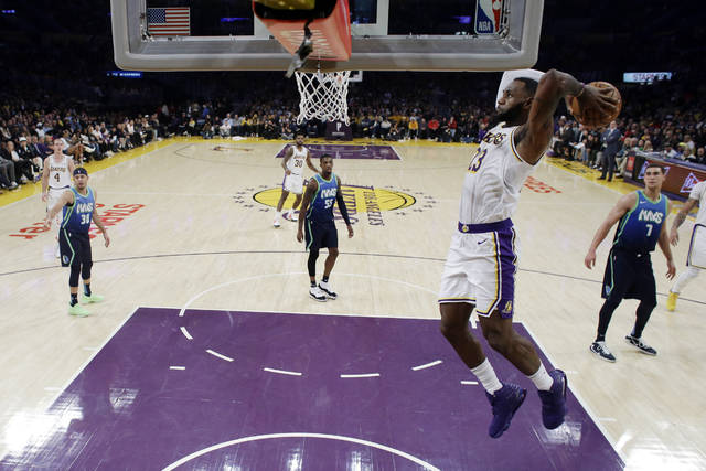 Los Angeles Lakers' LeBron James, right, dunks against the Dallas Mavericks during the second half of an NBA basketball game Sunday, Dec. 1, 2019, in Los Angeles. (AP Photo/Marcio Jose Sanchez)