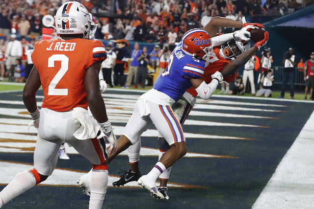 Virginia wide receiver Hasise Dubois (8) scores a touchdown against Florida defensive back Marco Wilson (3) during the first half of the Orange Bowl NCAA college football game, Monday, Dec. 30, 2019, in Miami Gardens, Fla. (AP Photo/Brynn Anderson)