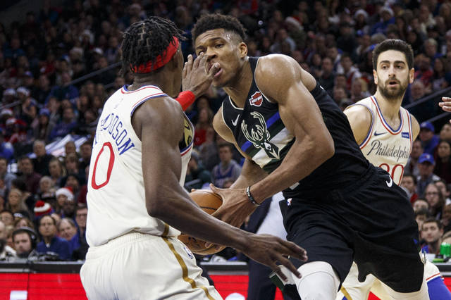 Milwaukee Bucks' Giannis Antetokounmpo, right, drives to the basket as Philadelphia 76ers' Josh Richardson, left, will accidentally pokes him in the eye during the second half of an NBA basketball game, Wednesday, Dec. 25, 2019, in Philadelphia. The 76ers won 121-109. (AP Photo/Chris Szagola)