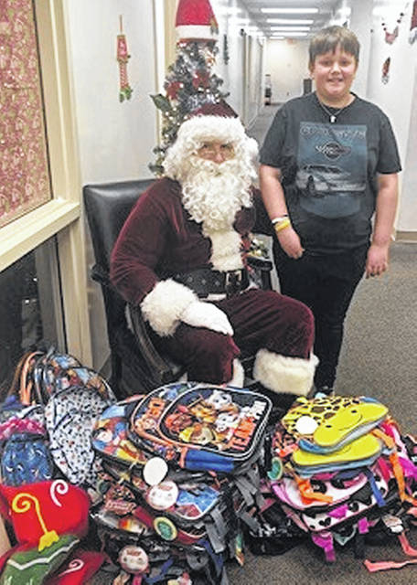"Aiden Poore, who organizes the ""Aiden's Buddy Bags"" project, is pictured with Santa Claus."