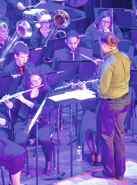 Eric Stanton festively conducts the Clinton County Community Band during their concert at the Murphy Theatre at Saturday's Hometown Holidazzle.