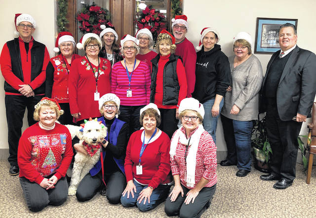 """Clinton County CASA volunteers met for their monthly """"CASA Coffee"""", a monthly in-service training and peer networking opportunity for those serving as child advocates. The volunteers donned Santa hats and posed for a photo with Juvenile Court Judge Chad L. Carey and Ernie, the CASA mascot, and goldendoodle puppy of CASA Director Kim Vandervort and her husband and volunteer, Kent Vandervort. Pictured seated in the front row from left are volunteers Laura McGuire, Ernie with Kim Vandervort, Kathy Vincent and Bobbie Sampson; and standing from left are Kent Vandervort, Becky Miller, Gail Satterthwaite, Deb Daugherty, Lorry Swindler, Mary Conger, Beverly Drapalik, Jeff Drapalik, Mary Quigley, Diana Groves, and Judge Carey. Not pictured are CASA volunteers Elizabeth Biggane, Sandy Bigley, Kenna Edwards, Tonia Farley, Barbara Glass, Judy Johnston, Debra Moore and Tarah Mongold. For information on the CASA program call 937-383-1137."""