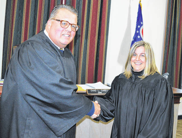 Chaley Peelle Griffith, right, shakes hands with Clinton County Juvenile/Probate Judge Chad Carey after she was sworn in Monday as Juvenile/Probate magistrate. Her father, William Peelle, also practices law and ceremoniously helped his daughter don a judicial robe prior to the photo.