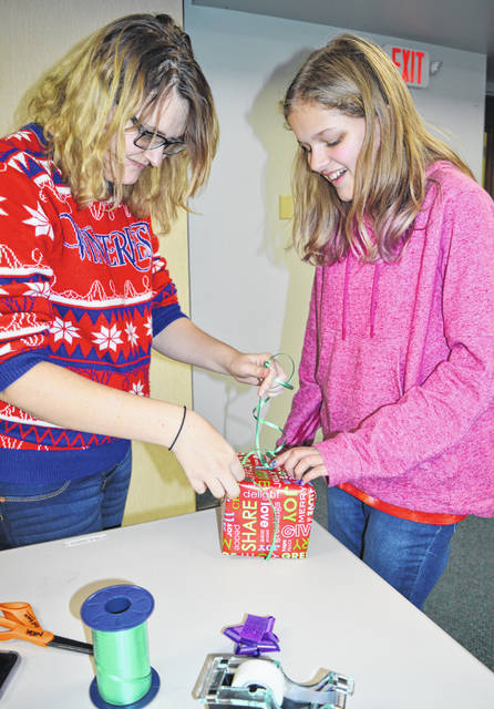 When tying a ribbon around a boxed gift, three hands are better than two. From left are Wilmington Public Library teen librarian Nikia Granger and Scarlett Cucculelli.