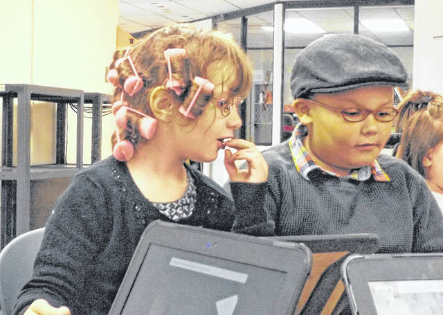 "Kindergarten students at Holmes Elementary School in Wilmington were asked to dress like they are 100 on Monday to observe their 100th day of being in school. Reportedly some of the kindergarten kids ""felt big"" now that they've been a school student for 100 days. From left are Ava Gibson in hair curlers and Malachi Murdock wearing a men's beret cap. The veteran kindergartners are practicing computer skills."