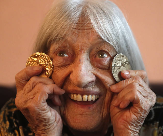 Agnes Keleti, former Olympic gold medal winning gymnast, poses for a photo with two of her Olympic medals at her apartment in Budapest, Hungary Wednesday Jan. 8, 2020. Although she turned 99 on Thursday, even a 9-year-old would have a hard time keeping up with Agnes Keleti's irrepressible energy and enthusiasm. Keleti is the oldest living Olympic champion and a Holocaust survivor. She won 10 medals in gymnastics — including five golds — at the 1952 Helsinki Games and at the 1956 Melbourne Games. (AP Photo/Laszlo Balogh)