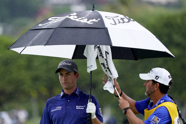 Webb Simpson keeps dry as his caddie dries off his club on the 13th green during the final round of the Sony Open PGA Tour golf event, Sunday, Jan. 12, 2020, at Waialae Country Club in Honolulu. (AP Photo/Matt York)