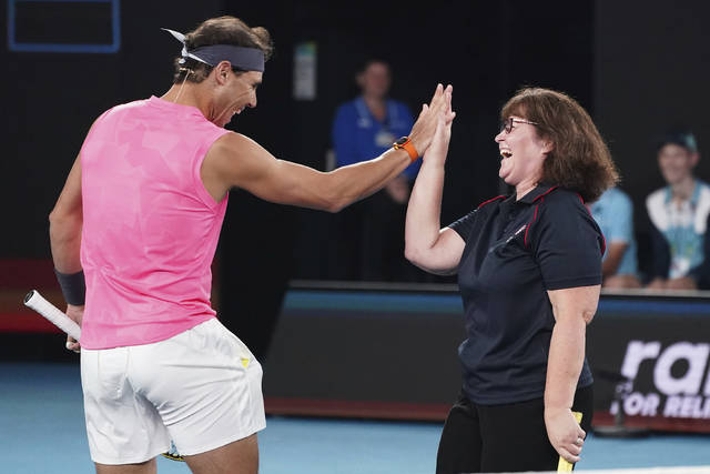 Rafael Nadal of Spain, left, and Deb Boirg, an Australian firefighter celebrate as they play a game of tennis together during the Rally For Relief at Rod Laver Arena in Melbourne, Wednesday, Jan. 15, 2020. Tennis stars have come together for the Rally for Relief to raise money in aid of the bushfire relief efforts across Australia. (Scott Barbour/AAP Image via AP)