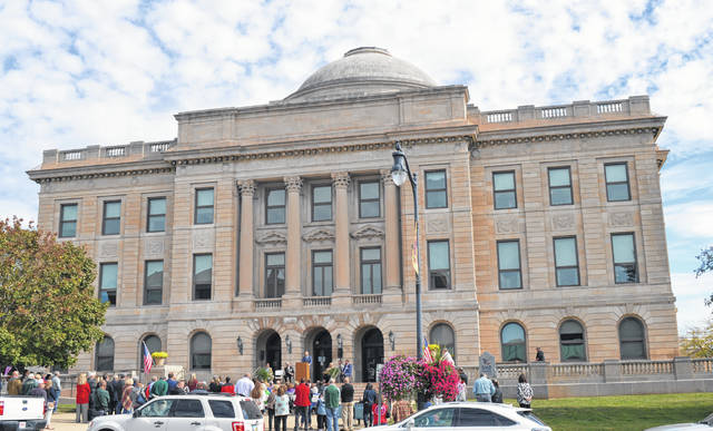 Approximately 150 people gather outside the Clinton County Courthouse on a Saturday for the afternoon portion of events celebrating the building's centennial. Many people attended the earlier open house that included historical talks, tours of the various departments and historical displays.