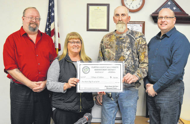 Clinton County Solid Waste Management District Coordinator Jeff Walls, far right, awards funds to Sabina to assist with the town's annual community cleanup event. From left are Sabina Mayor Jim Mongold, Clinton County Commissioner Brenda Woods, Sabina Village Administrator Rob Dean, and Walls.