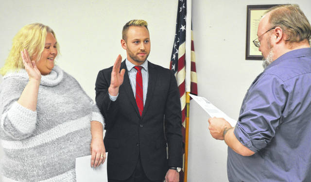 From left, Bethany Grehl and Benjamin Collings are sworn in as new members of Sabina Village Council by new Mayor Jim Mongold.