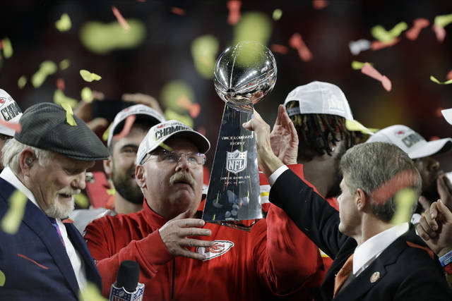Kansas City Chiefs chairman Clark Hunt, right, hands the trophy to head coach Andy Reid after the chiefs defeated the San Francisco 49ers in the NFL Super Bowl 54 football game Sunday, Feb. 2, 2020, in Miami Gardens, Fla. (AP Photo/Chris O'Meara)