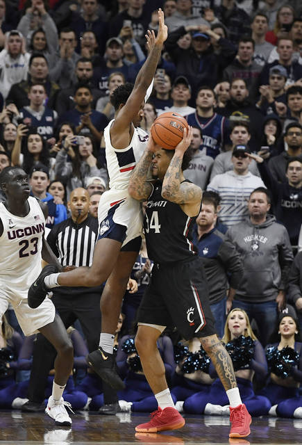 Connecticut's Christian Vital makes contact with Cincinnati's Jarron Cumberland, right, at the buzzer of overtime in an NCAA college basketball game, Sunday, Feb. 9, 2020, in Storrs, Conn. (AP Photo/Jessica Hill)
