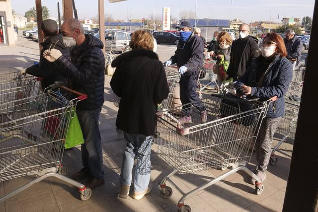 People queue outside a supermarket in Casalpusterlengo, Northern Italy, Monday, Feb. 24, 2020. Italy scrambled to check the spread of Europe's first major outbreak of the new viral disease amid rapidly rising numbers of infections and a third death. Road blocks were set up in at least some of 10 towns in Lombardy at the epicenter of the outbreak, including in Casalpusterlengo, to keep people from leaving or arriving. (AP Photo/Paolo Santalucia)