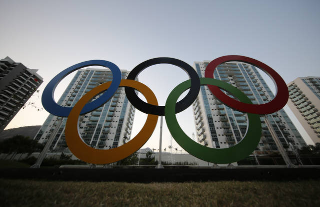 FILE - In this July 23, 2016, file photo, a representation of the Olympic rings are displayed in the Olympic Village in Rio de Janeiro, Brazil. An eye-opening survey finds that the majority of elite and Olympic athletes struggle to make ends meet. 58 percent of the 491 respondents from across the globe said they did not consider themselves financially stable. (AP Photo/Leo Correa, File)