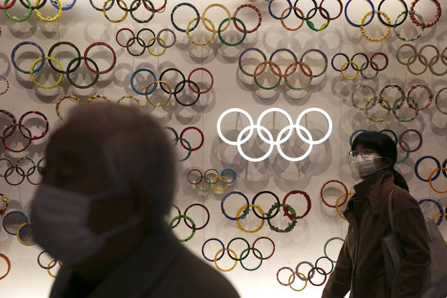 Two people wear masks as they visit the newly opened Japan Olympic Museum located near the New National Stadium, Sunday, Feb. 23, 2020, in Tokyo. (AP Photo/Jae C. Hong)