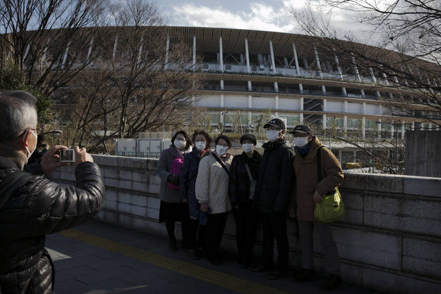 Tourists wear masks as they pause for photos with the New National Stadium, a venue for the opening and closing ceremonies at the Tokyo 2020 Olympics, Sunday, Feb. 23, 2020, in Tokyo. (AP Photo/Jae C. Hong)