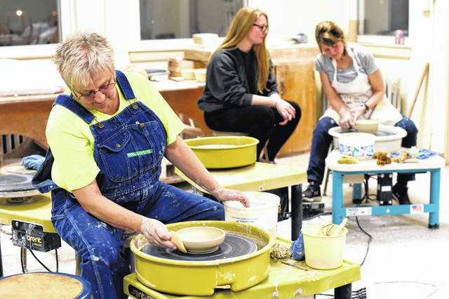 Local ceramicist Diane Anderson, left, works the potter's wheel while a WC student, Katelyn Hill, observes ceramics instructor Michele Carr in the College's ceramics studio.