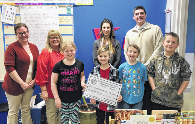 Clinton-Massie students are pictured receiving their grant award. From left are, front, Kate D., Jackson R., Cayden P., and Jimmy G; and, back, SWMD Outreach Specialist Erin Hartsock, County Commissioner Brenda Woods, teacher Jen Molitor, and Clinton-Massie Superintendent Matt Baker.