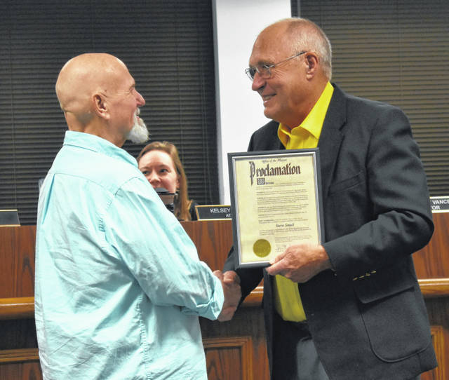 Retired clinical manager of Clinton Medical Transport (CMT) Steve Small, left, gets a handshake from Mayor John Stanforth after being recognized for his 43 years of service at Thursday's Wilmington City Council meeting.