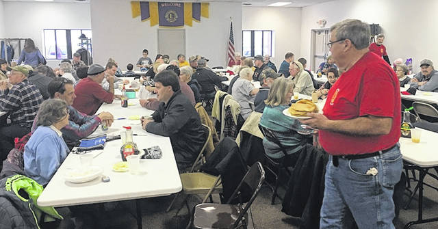 The New Vienna Lions Club was pleased with the turnout at its annual Pancake Day. In the right foreground walking with a plate of pancakes is Wayne Ames.
