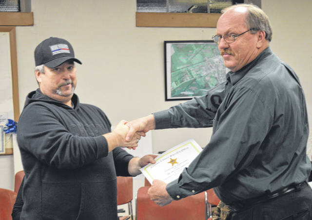 Sabina Police Sgt. John Grehl, left, is recognized and congratulated for his action in response to a shooting call from another jurisdiction. At right is Sabina Chief of Police Keynon Young.