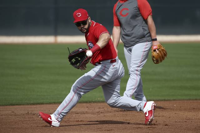 Cincinnati Reds third baseman Eugenio Suarez fields a grounder during baseball spring training Friday, Feb. 21, 2020, in Goodyear, Ariz. (AP Photo/Ross D. Franklin)