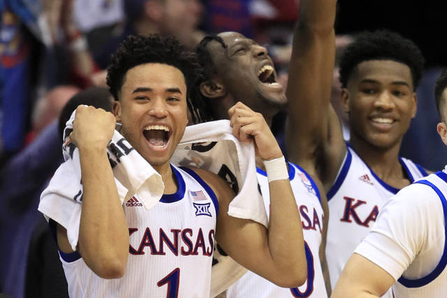 Kansas guards Devon Dotson (1), Marcus Garrett (0) and Ochai Agbaji, right, celebrate a teammates basket during the second half of an NCAA college basketball game against Iowa State in Lawrence, Kan., Monday, Feb. 17, 2020. Dotson scored 29 points in the game. Kansas defeated Iowa State 91-71. (AP Photo/Orlin Wagner)